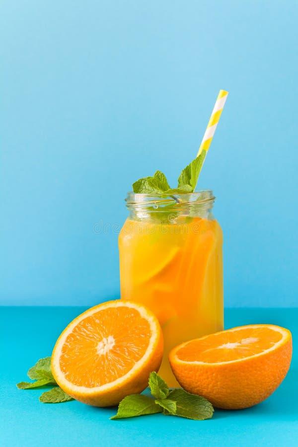 Flasche mit orange Limonade, verziertem Eis und Minze lizenzfreies stockfoto