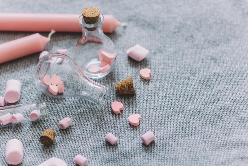 Flasche mit rosa Schokoladenherzen, Eibische, Kerzen stockfoto