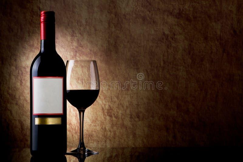 Flasche mit Rotwein und Glas auf einem alten Stein stockfotografie