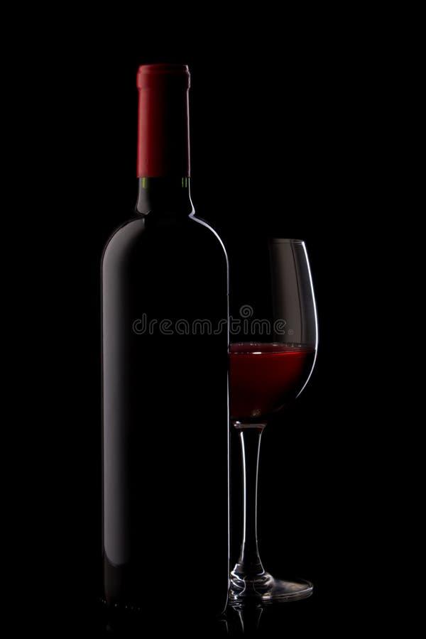 Flasche mit Rotwein und Glas auf einem Schwarzen stockfoto