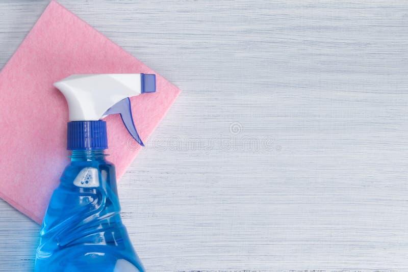 Flasche mit Spray mit Reinigungsflüssigkeit, auf einem rosa Lappen, auf einem hellen Hintergrund, mit einem Platz für die Aufschr lizenzfreie stockbilder