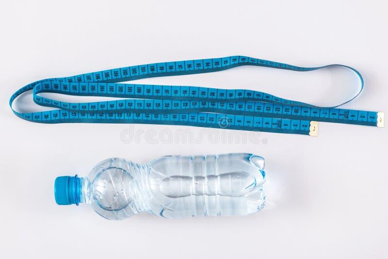 Flasche mit Wasser und Maßband lizenzfreie stockbilder