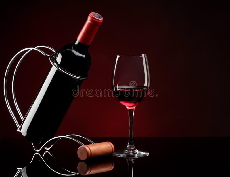Flasche mit Wein auf einem Standplatz und einem Glas stockbild