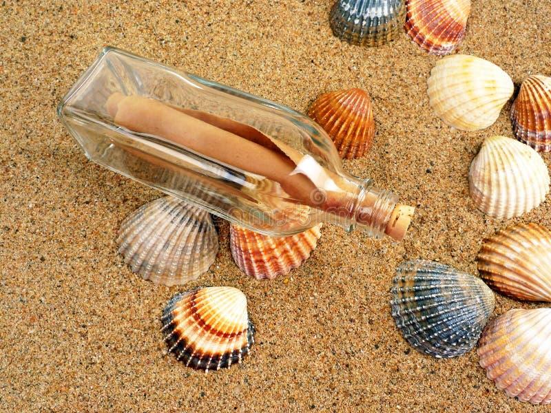 Flasche mit Zeichen auf einem Strand stockfoto