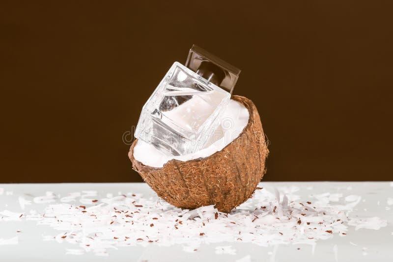 Flasche Parfüm mit frischer Kokosnuss auf Tabelle gegen schwarzen Hintergrund lizenzfreies stockbild