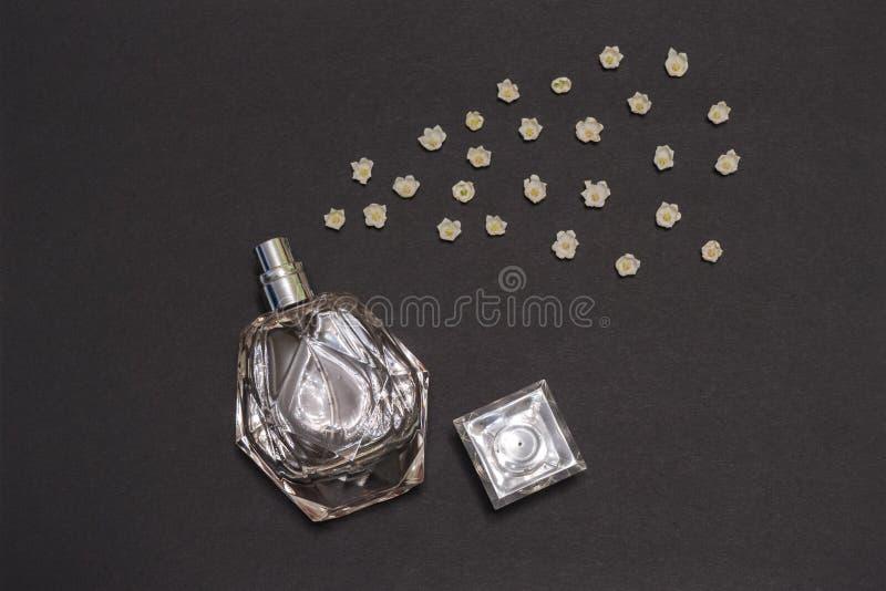 Flasche Parfüm- und Maiglöckchenblumenknospen auf schwarzem Hintergrund Parfümerie, Duft, kosmetisches Konzept Frühling oder lizenzfreie stockfotografie