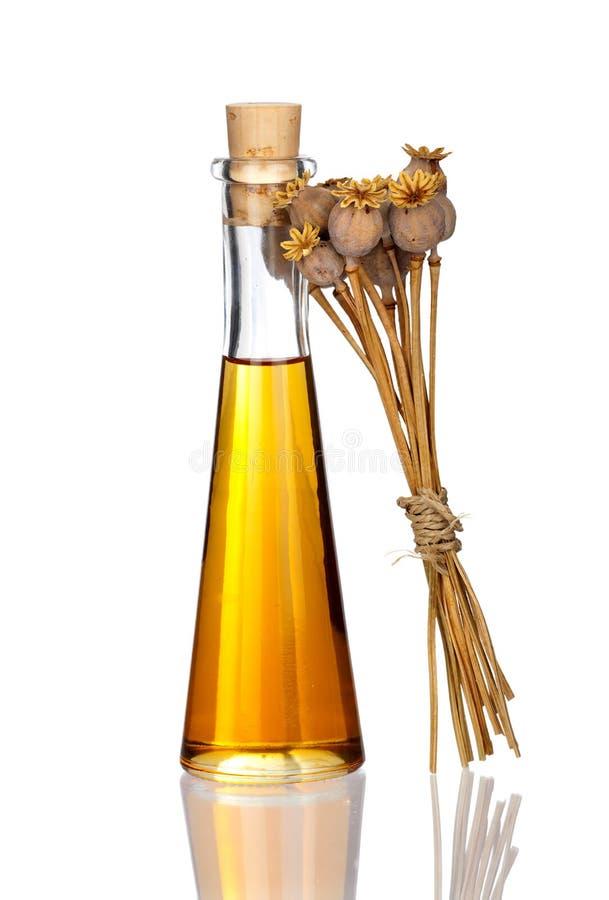 Flasche Poppy Seed Oil und getrocknete Köpfe mit wirklicher Reflexion lizenzfreie stockfotos