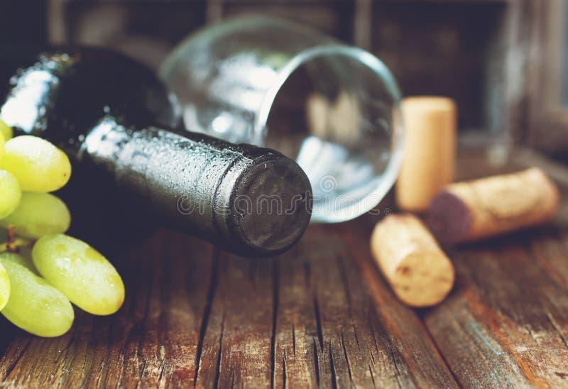 Flasche Rotwein mit frischer Traube und Bündel Korken auf Holztisch lizenzfreies stockfoto