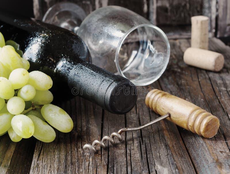 Flasche Rotwein mit frischer Traube und Bündel Korken auf Holztisch lizenzfreie stockfotos