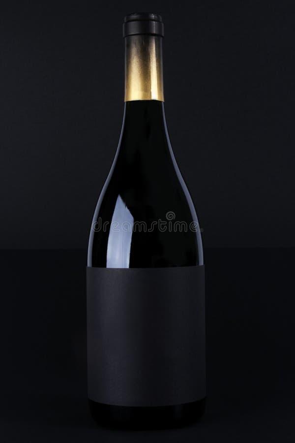 Flasche Rotwein mit schwarzem Hintergrund lizenzfreies stockfoto