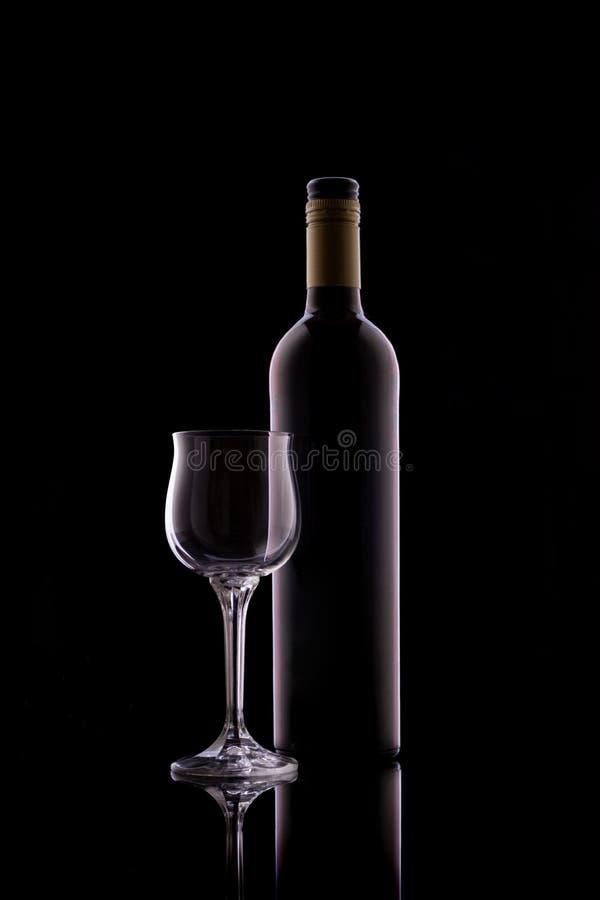 Flasche Rotwein und leere Glaskugel lizenzfreies stockbild