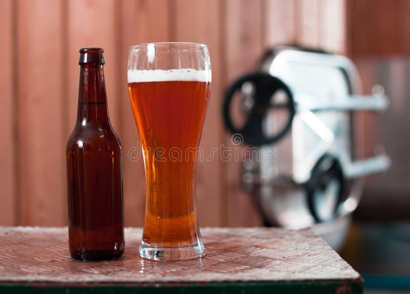Flasche und Glas mit Goldbier auf dem Hintergrund von Fässern für stockfotografie
