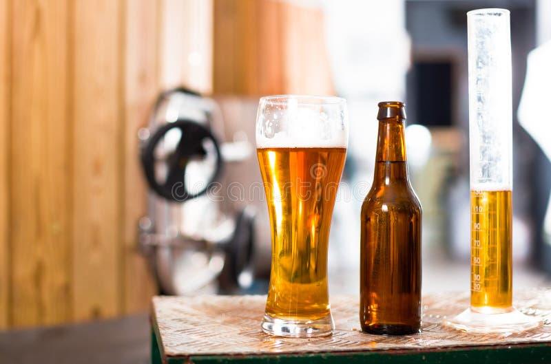 Flasche und Glas mit Goldbier auf dem Hintergrund von Fässern für lizenzfreie stockbilder
