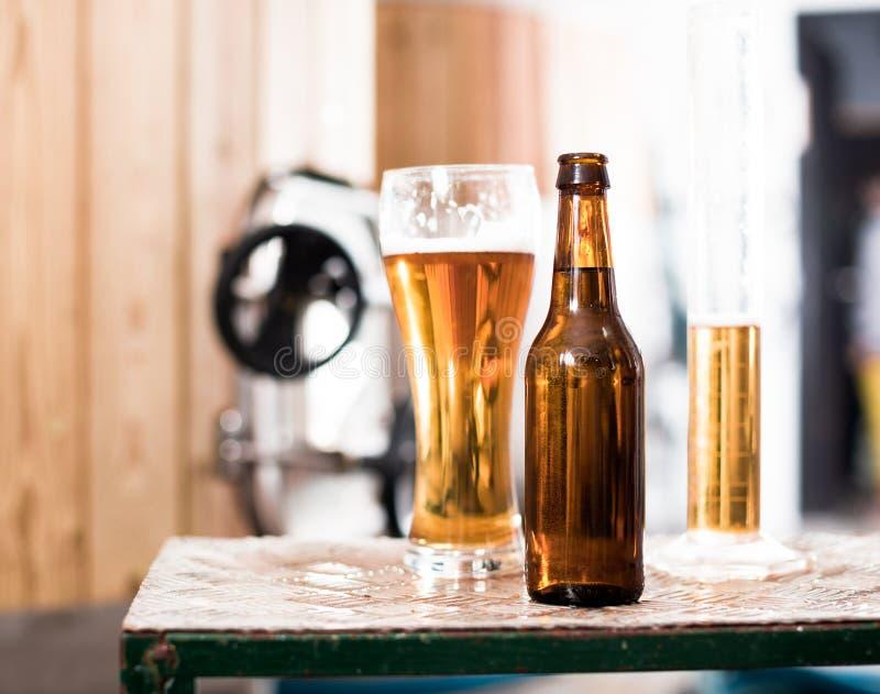 Flasche und Glas mit Goldbier auf dem Hintergrund von Fässern für stockfotos