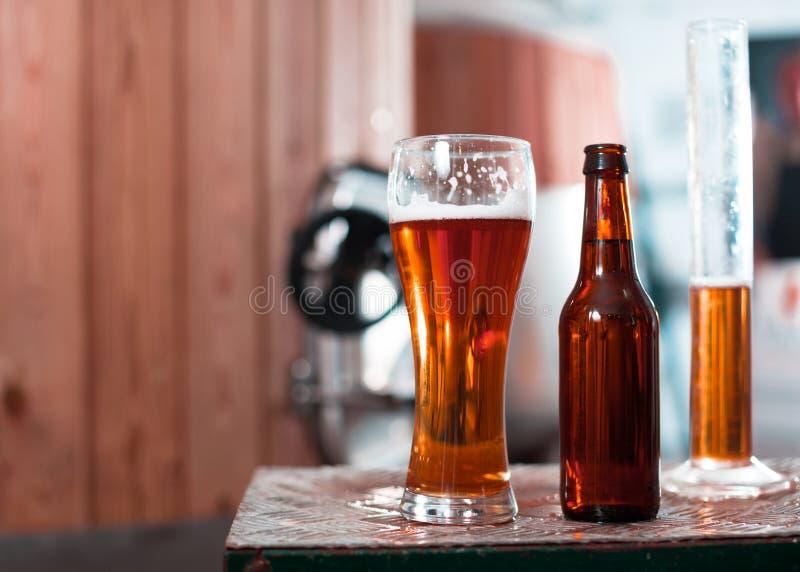 Flasche und Glas mit Goldbier auf dem Hintergrund von Fässern für stockfoto