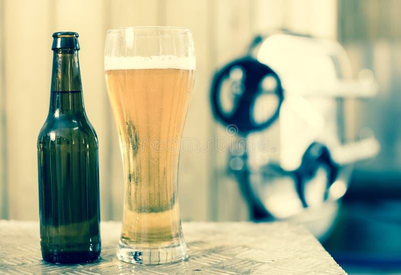 Flasche und Glas mit Goldbier auf dem Hintergrund von Fässern für lizenzfreies stockfoto