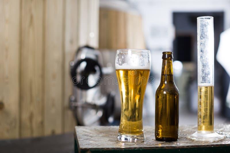 Flasche und Glas mit Goldbier auf dem Hintergrund von Fässern für Gärung lizenzfreie stockfotografie
