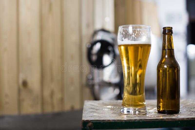 Flasche und Glas mit Goldbier auf dem Hintergrund von Fässern für Gärung lizenzfreie stockfotos