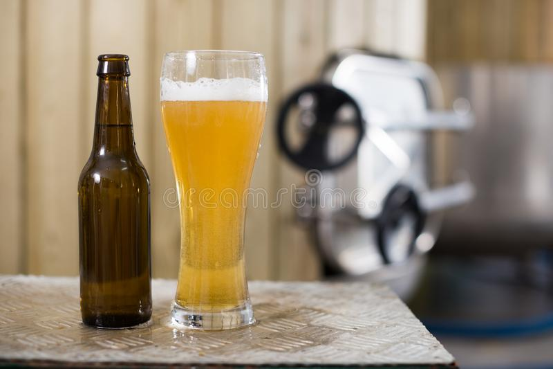 Flasche und Glas mit Goldbier auf dem Hintergrund von Fässern für Gärung stockbild