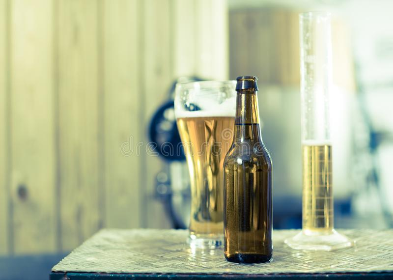 Flasche und Glas mit Goldbier auf dem Hintergrund von F?ssern f?r G?rung lizenzfreie stockfotos