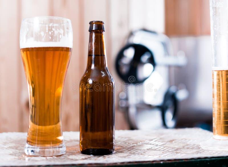 Flasche und Glas mit Goldbier auf dem Hintergrund von F?ssern f?r G?rung lizenzfreies stockbild