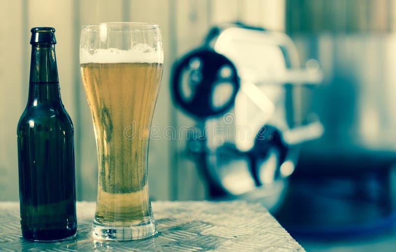 Flasche und Glas mit Goldbier auf dem Hintergrund von F?ssern f?r G?rung lizenzfreie stockbilder
