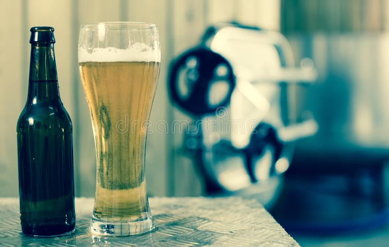 Flasche und Glas mit Goldbier auf dem Hintergrund von F?ssern f?r G?rung lizenzfreies stockfoto