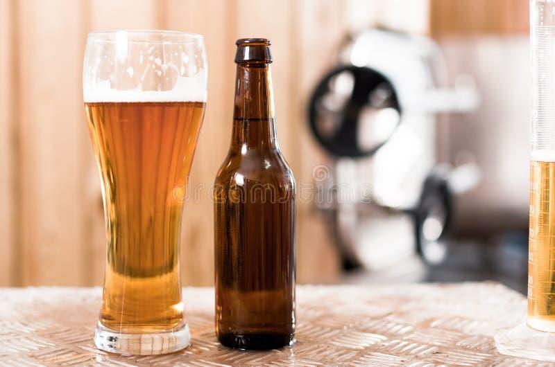 Flasche und Glas mit Goldbier auf dem Hintergrund von F?ssern f?r G?rung stockfotografie