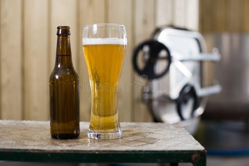 Flasche und Glas mit Goldbier auf dem Hintergrund von F?ssern f?r G?rung stockfoto