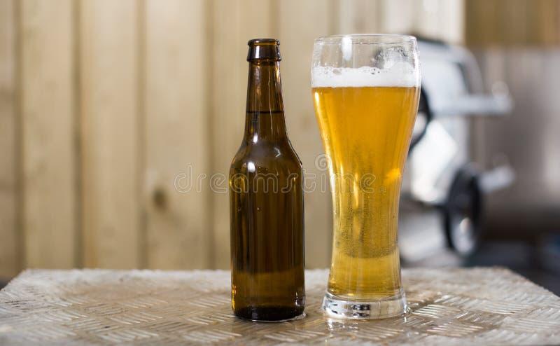 Flasche und Glas mit Goldbier auf dem Hintergrund von F?ssern f?r G?rung lizenzfreie stockfotografie