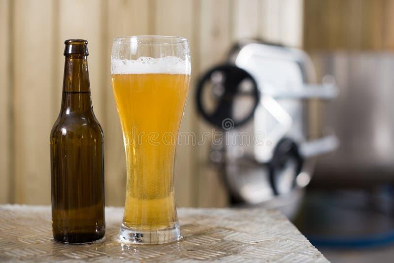 Flasche und Glas mit Goldbier auf dem Hintergrund von F?ssern f?r G?rung stockbild
