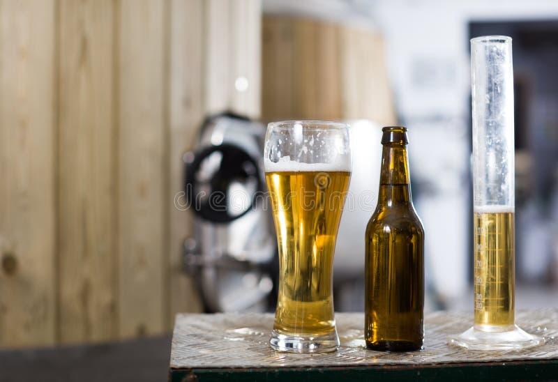 Flasche und Glas mit Goldbier auf dem Hintergrund von F?ssern f?r G?rung stockbilder