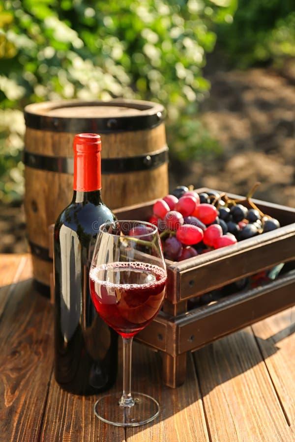 Flasche und Glas Rotwein mit frischen Trauben auf Holztisch im Weinberg lizenzfreies stockfoto