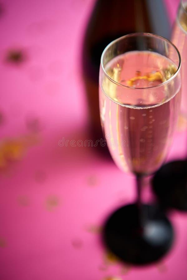 Flasche und zwei Gläser voll von funkelndem Champagnerwein mit goldener Dekoration lizenzfreie stockfotos