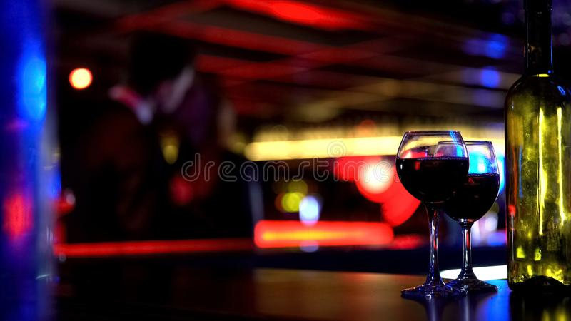 Flasche Wein mit zwei Gläsern, junge Paare auf unscharfem Hintergrund küssend lizenzfreies stockfoto