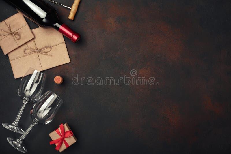 Flasche Wein, zwei Gläser, Geschenkbox, Umschlag, Korkenzieher und Korken, auf Draufsicht des rostigen Hintergrundes stockfoto