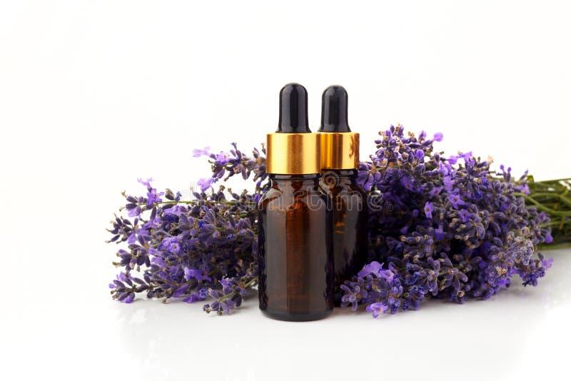 Flaschen mit den Aromaöl- und -lavendelblumen lokalisiert auf Weiß stockfotos