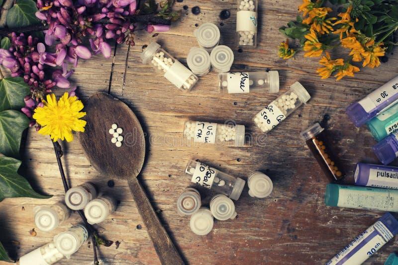 Flaschen mit den Homöopathiekügelchen und -löffel, verziert mit flowe lizenzfreie stockfotos
