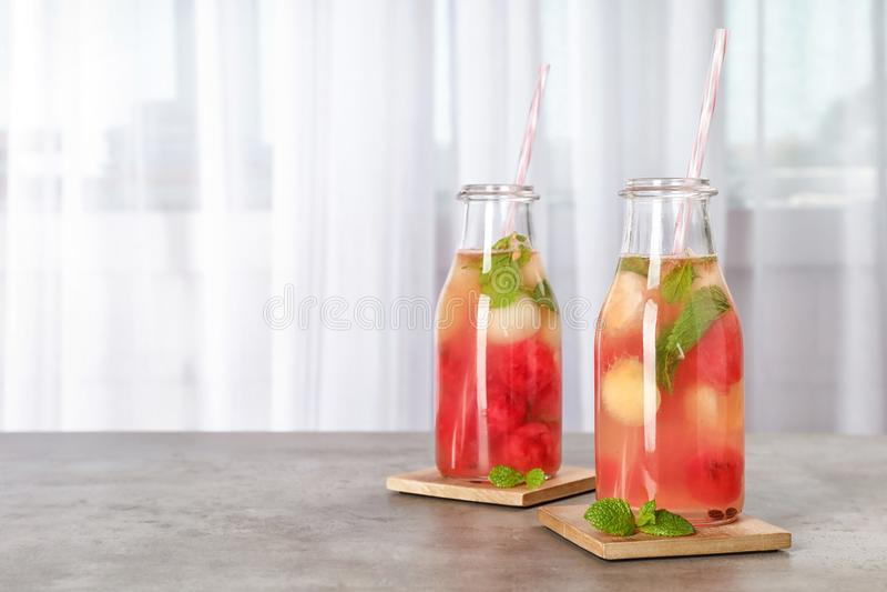 Flaschen mit geschmackvollem Wassermelonen- und Melonenball trinken stockbilder