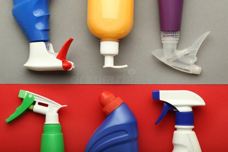Flaschen mit Reinigungsmitteln auf Farbhintergrund, flache Lage lizenzfreies stockfoto
