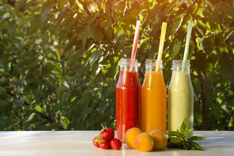 Flaschen mit Saft und Früchten auf einem grünen Hintergrund, Lebensmittel concep lizenzfreie stockfotos