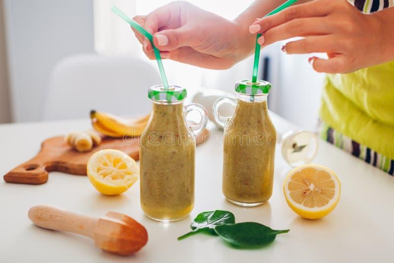 Flaschen mit Spinat und Banane Smoothie mit Bestandteilen Frau setzt Strohe in Getränke ein Gesunde Detoxdi?t stockfotos