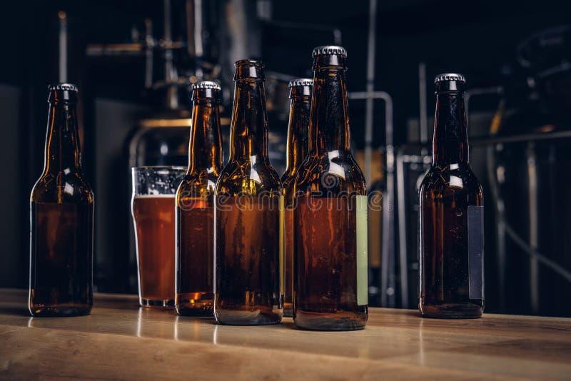 Flaschen und Glas Handwerksbier auf hölzernem Barzähler an der indie Brauerei stockbild
