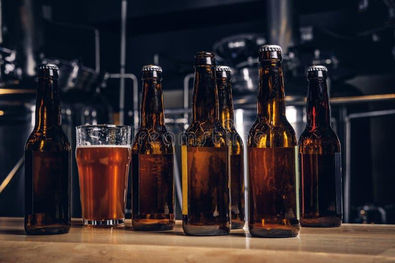 Flaschen und Glas Handwerksbier auf hölzernem Barzähler an der indie Brauerei stockfotografie