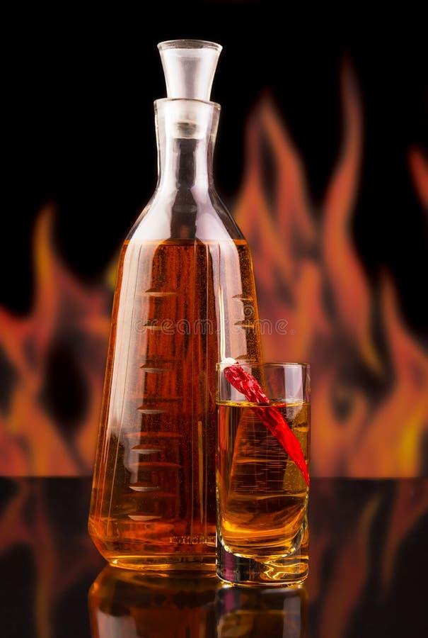 Flaschen- und Glaswodka mit Paprikapfeffer auf Hintergrundflammen lizenzfreie stockfotografie