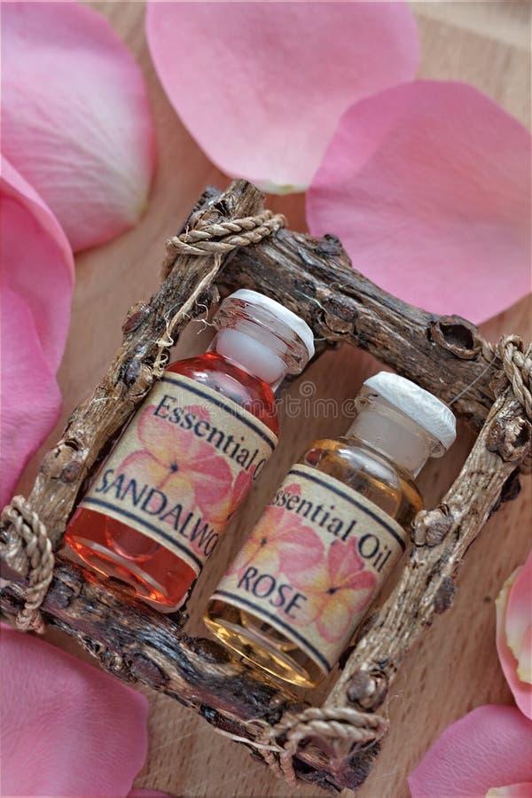 Flaschen von Rose Essence mit den Blumenblättern stockbilder