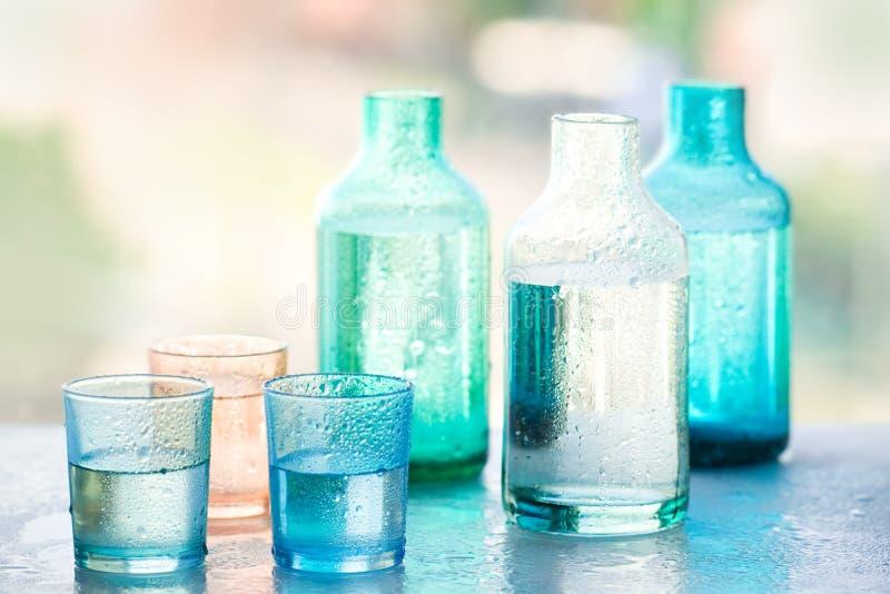 Flaschen Wasser und Gläser Wasser stockfotografie