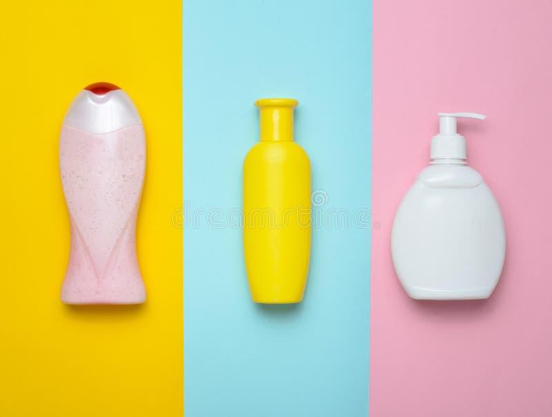 Flaschenprodukte für Dusche und Badezimmer auf einem mehrfarbigen Pastellhintergrund Shampoo, Flüssigseife, Duschgel Beschneidung lizenzfreie stockfotografie