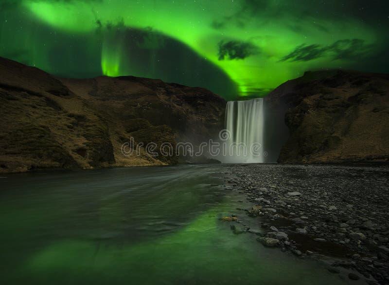 Flash dell'aurora polare sopra la cascata fotografia stock
