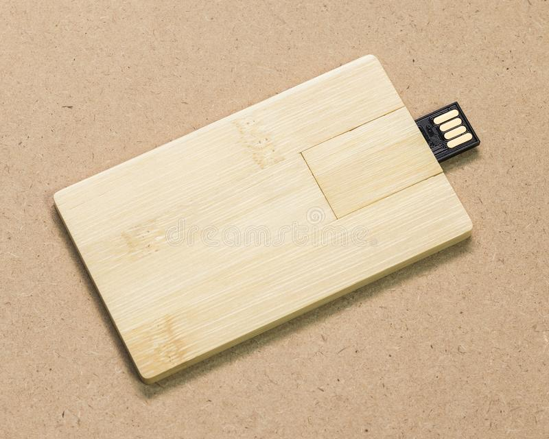 Flash drive card on brown cardboard texture background.  USB stick made from wood material concept. Flash drive card on brown cardboard texture background. USB royalty free stock photos